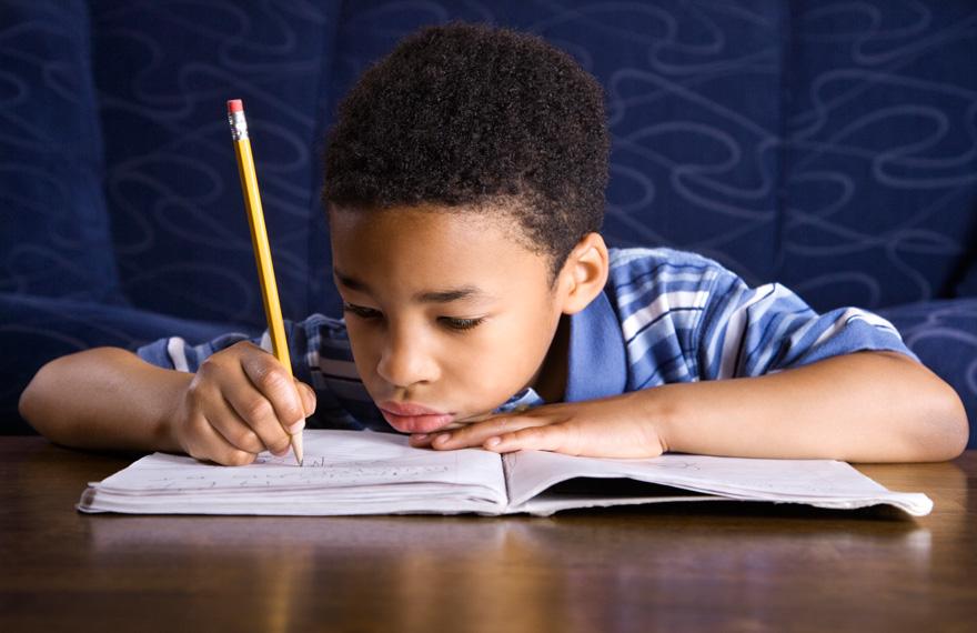 Boy Writing in Book at School