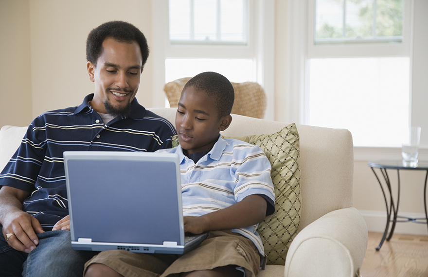 Young man and his son using a laptop