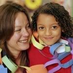Schoolgirl (5-7) with teacher, wearing paper chains, portrait