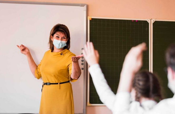 Teacher in mask stands at white erase board, students have hands raised.